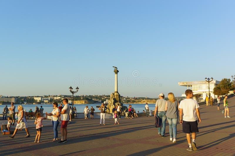 黑海市的码头的游人在纪念碑附近的对被破坏的船 库存图片