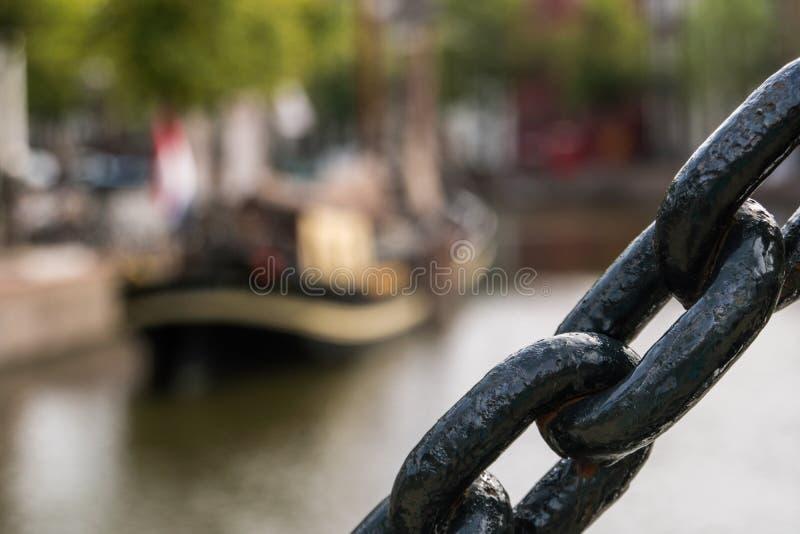 黑海链子关闭 与旗子的传统木在一个委员会的帆船和标志渠道的blured  库存图片