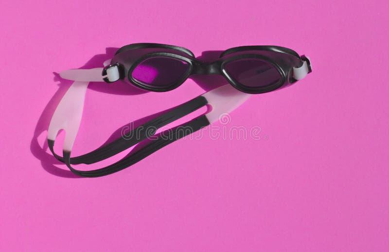 黑游泳的风镜,在桃红色背景,早晨阳光,运动员,视力保护的空白线路, 免版税库存照片