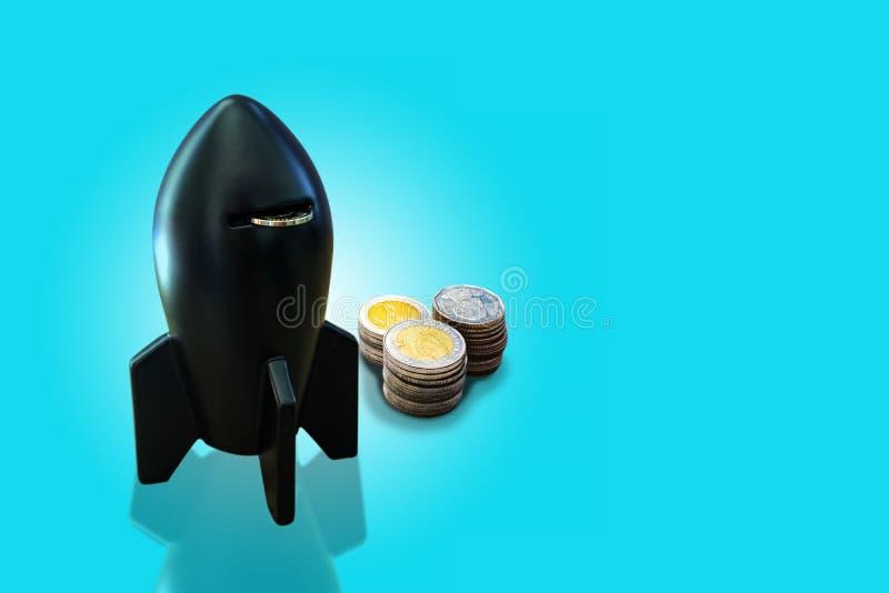 黑火箭形状硬币箱和金钱硬币在淡色蓝色背景堆积 火箭形状的存钱罐与硬币 r 免版税库存照片