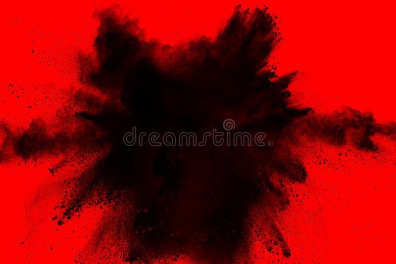 黑火药在红色背景隔绝的尘末爆炸 免版税库存图片