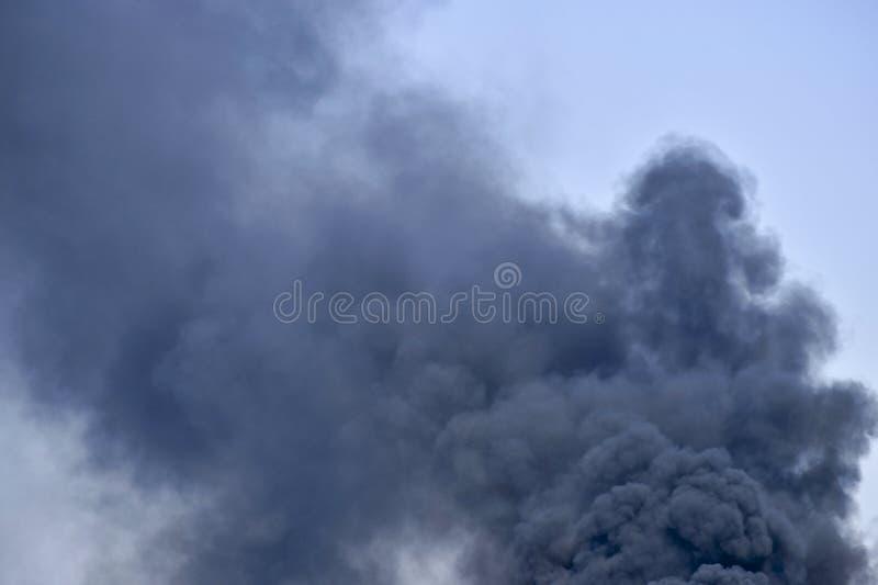 黑烟强有力的云彩反对天空的 背景 废物处置的问题 免版税图库摄影