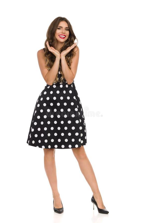 黑燕尾服的美丽的年轻女人在圆点在手和微笑上拿着头 免版税库存图片