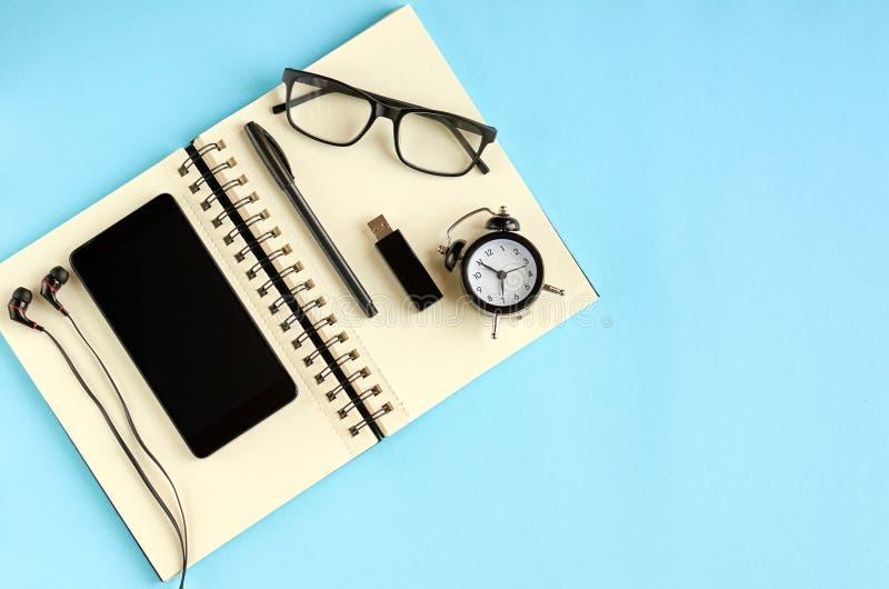 黑玻璃、手机、纸笔记薄、闹钟和耳机在蓝色背景构成 免版税库存照片