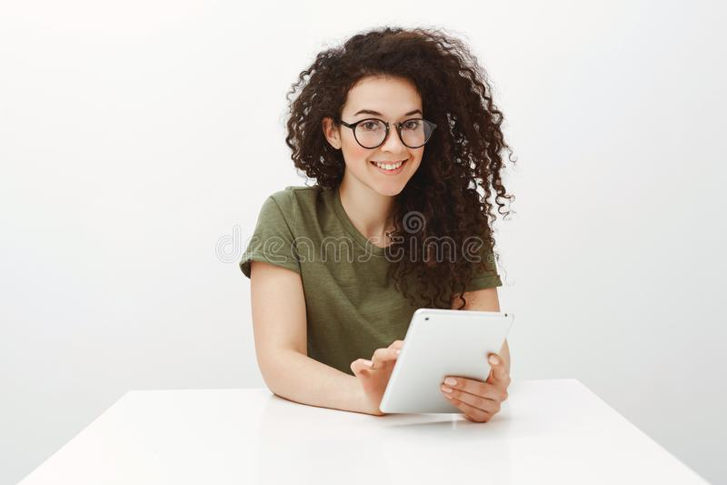 黑玻璃的,坐在白色桌上和浏览在网络的俏丽的浅黑肤色的男人室内射击通过数字式片剂 免版税库存照片