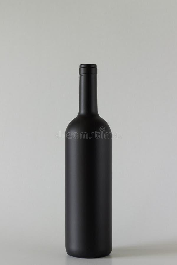 黑瓶在灰色背景的酒 免版税库存图片