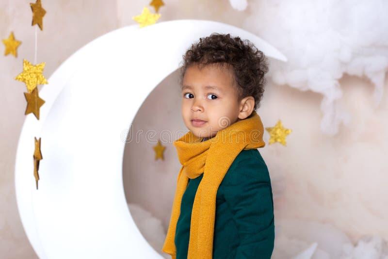 黑男孩关闭 一个快乐的微笑的男孩的画象一条黄色围巾的 小的非裔美国人的画象 沉思的黑人 免版税库存照片