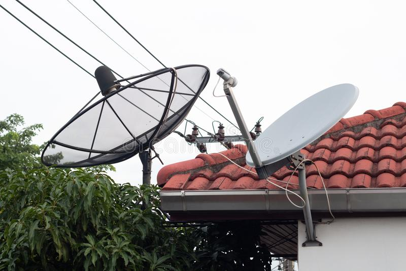 黑白卫星盘和电视天线在老村庄,抛物面数字接收机通信数据的关于roo 库存图片
