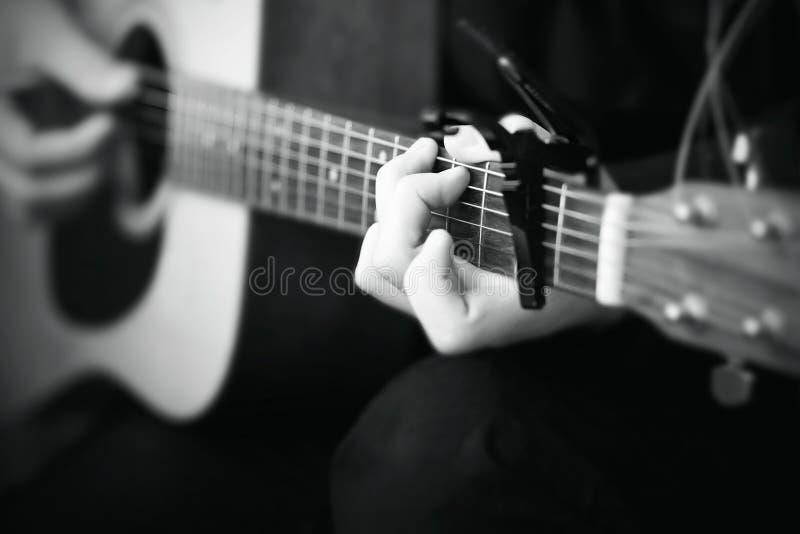 黑白图象,其中人播放在一把声学吉他的一支曲调 图库摄影