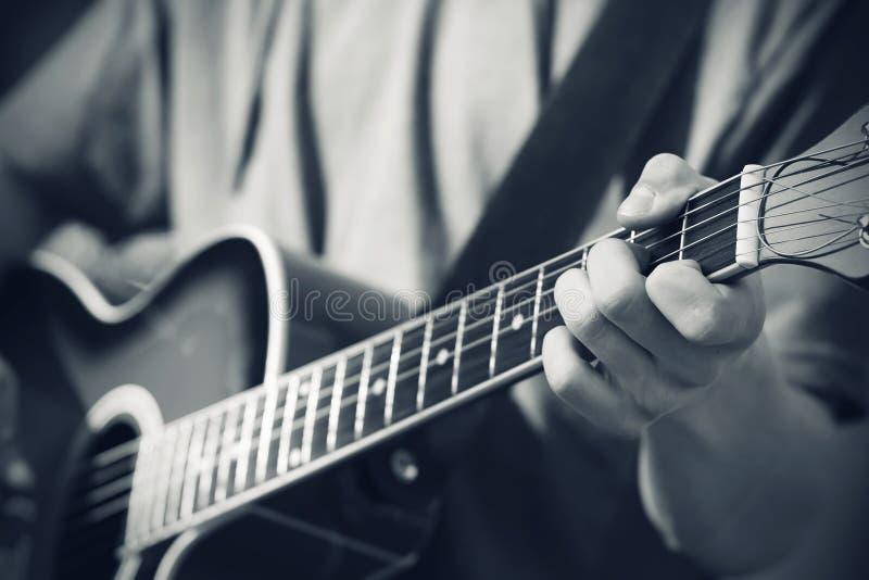黑白图象,其中音乐家播放在吉他的一支曲调 库存图片