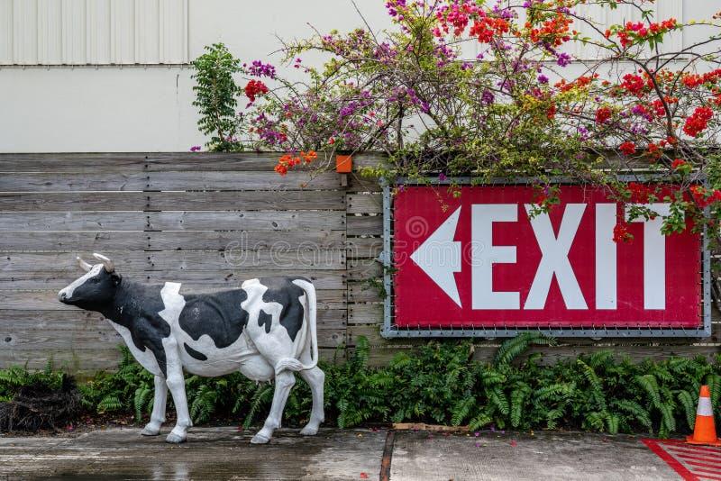 黑白母牛雕象和出口标志 免版税图库摄影