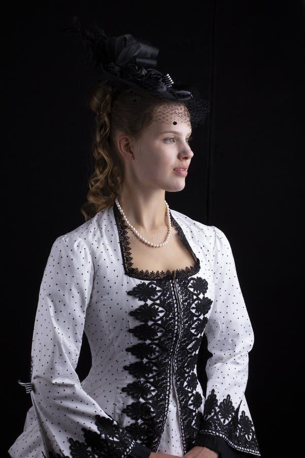 黑白熙来攘往礼服和帽子的维多利亚女王时代的妇女 免版税库存照片