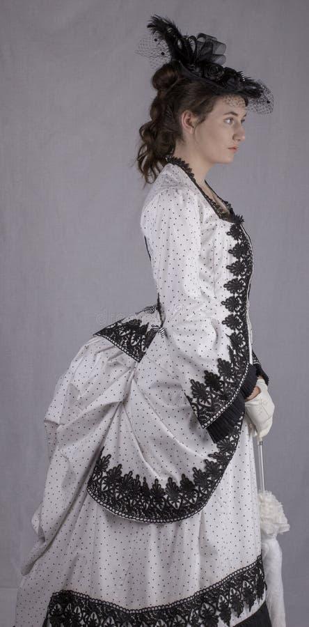 黑白熙来攘往礼服的维多利亚女王时代的妇女 图库摄影