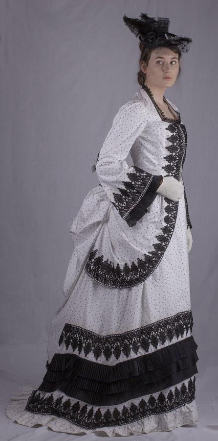 黑白熙来攘往礼服的维多利亚女王时代的妇女 库存照片
