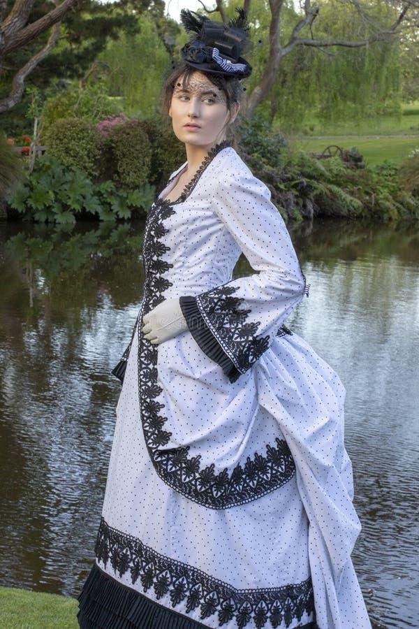 黑白熙来攘往礼服身分的维多利亚女王时代的妇女在庭院里 库存照片