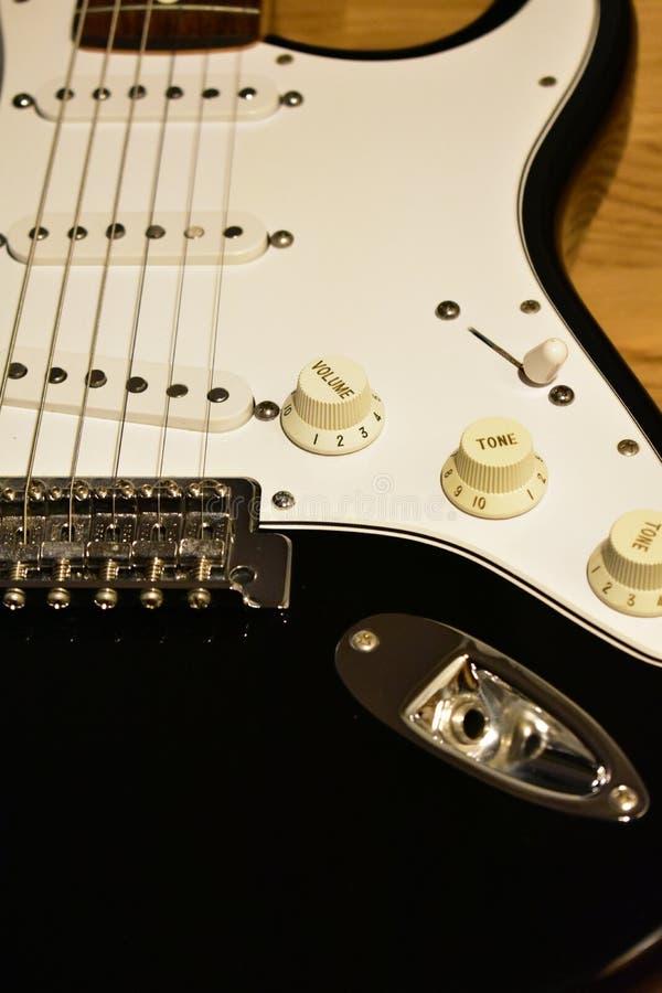 黑白电吉他细节 特写镜头:身体、桥梁、唯一卷提取、串、起重器、瘤、开关和pickguard 免版税库存照片