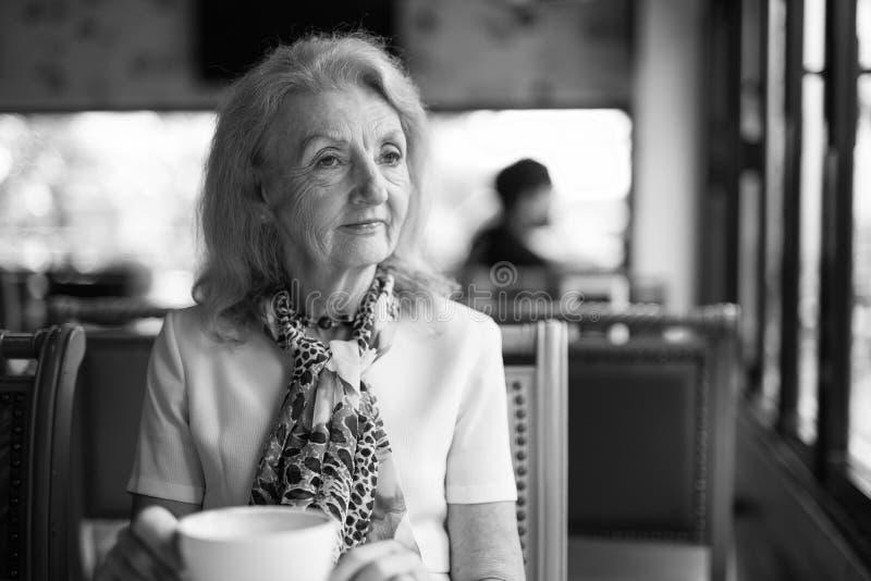 黑白画象资深年长妇女饮用的咖啡和看在窗口外面 免版税库存图片
