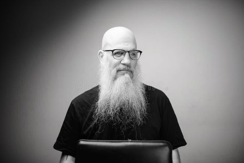 黑白眼镜中长着灰色长胡子的体贴成熟秃子 免版税库存图片