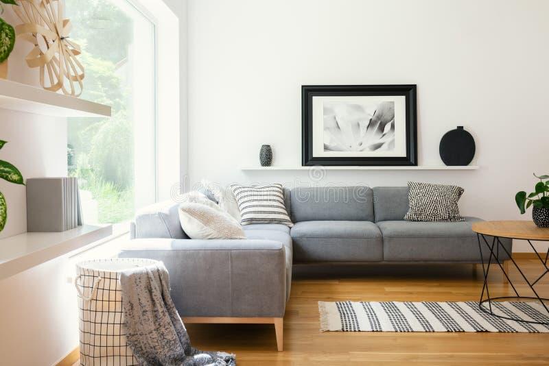 黑白纺织品和装饰在经典斯堪的纳维亚样式客厅内部与木家具和自然su 免版税库存照片