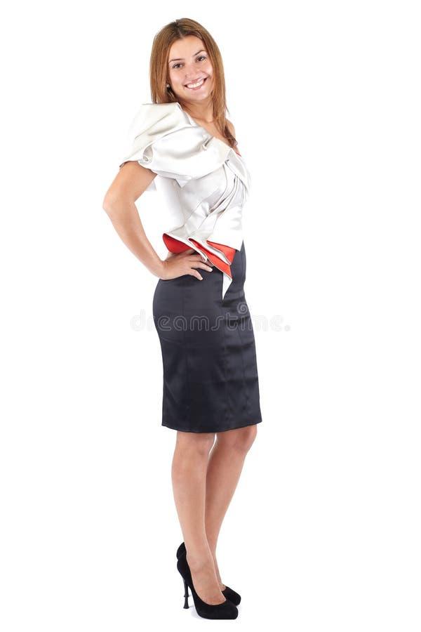 黑白色红色礼服的微笑的美丽的年轻女人,站立斜向一边和看照相机 演播室射击,充分的身体,被隔绝 免版税库存照片