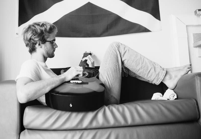 黑白葡萄酒图象样式中部说谎在沙发和使用在吉他的被射击年轻少年在青少年的屋子里 库存图片