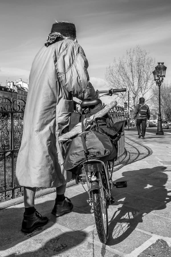 黑白观点的有一辆自行车和一颗典型的法国长方形宝石的一名妇女在巴黎中部,法国街道上  库存照片