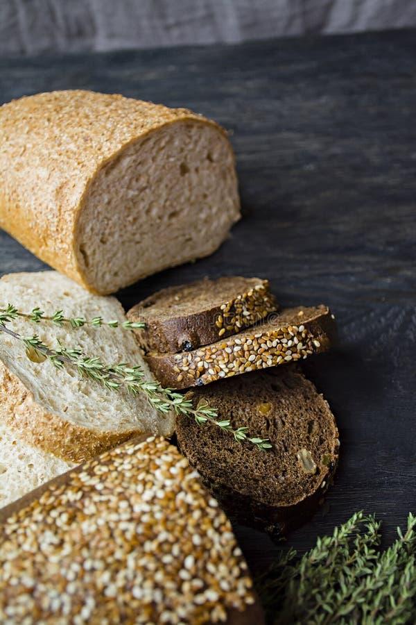 黑白面包大面包在黑委员会背景的 静物画,夺取从边 库存照片