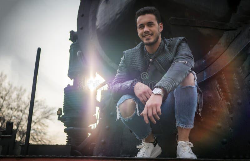 黑皮夹克的年轻人在老火车附近 免版税库存照片