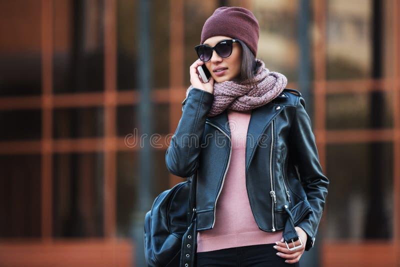 黑皮夹克的年轻时尚妇女使用在城市街道的手机 免版税库存照片
