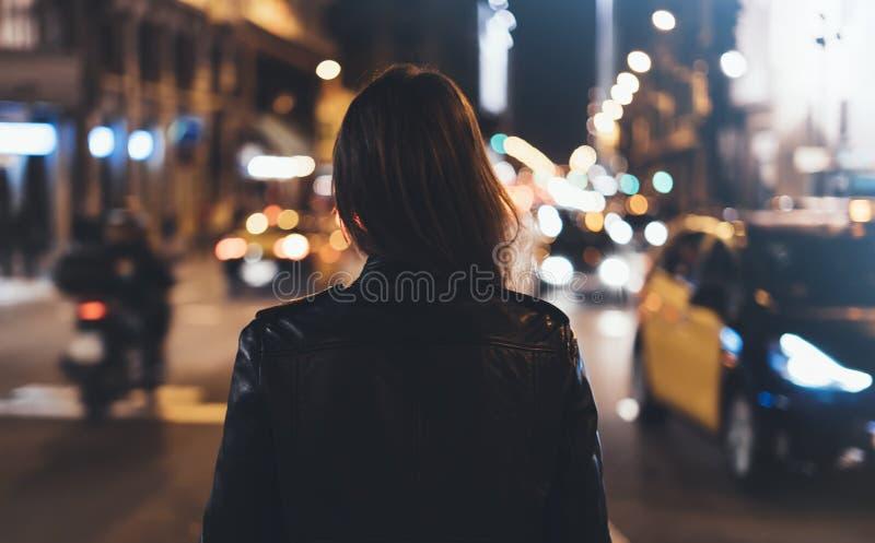 黑皮夹克的行家女孩从在背景照明焕发bokeh光的后面在夜大气圣诞节城市,喂 免版税库存照片