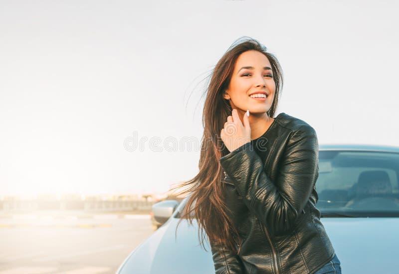 黑皮夹克的Happpy美丽的迷人的深色的长发年轻亚裔妇女在她的汽车附近 库存照片