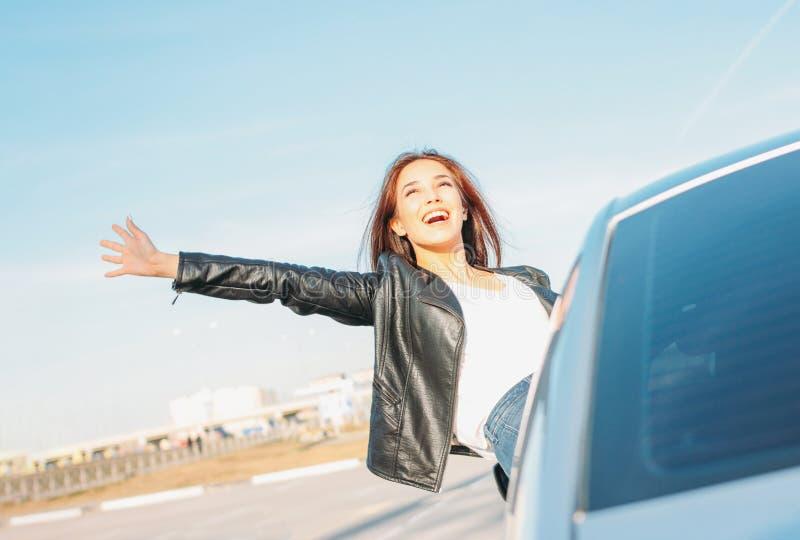 黑皮夹克的Happpy美丽的迷人的深色的长发年轻亚裔妇女在日落的车窗里 图库摄影