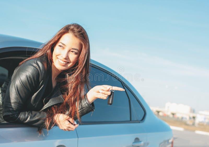 黑皮夹克的Happpy美丽的迷人的深色的长发年轻亚裔妇女有钥匙的在车窗里 免版税库存照片