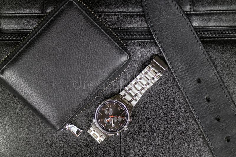 黑皮革、钱包、传送带和钢手表精神时髦的辅助部件在一个黑公文包的背景 免版税库存图片