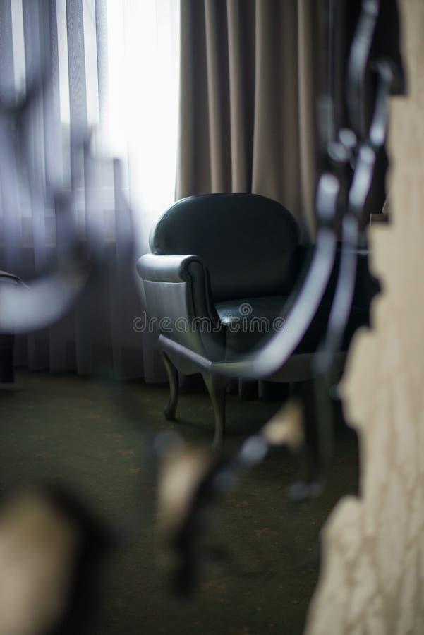 黑皮革扶手椅子通过在一个框架的镜子在地板上在一个暗室有窗口的背景 免版税图库摄影