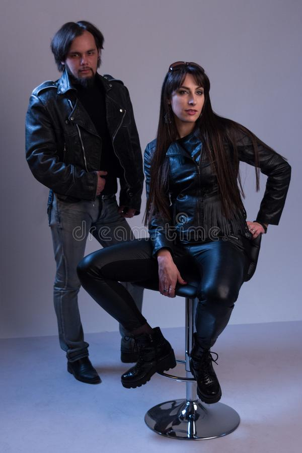 黑皮革衣裳的一个人在女孩旁边站立坐高凳 演播室photosession 现代时兴时髦 免版税图库摄影