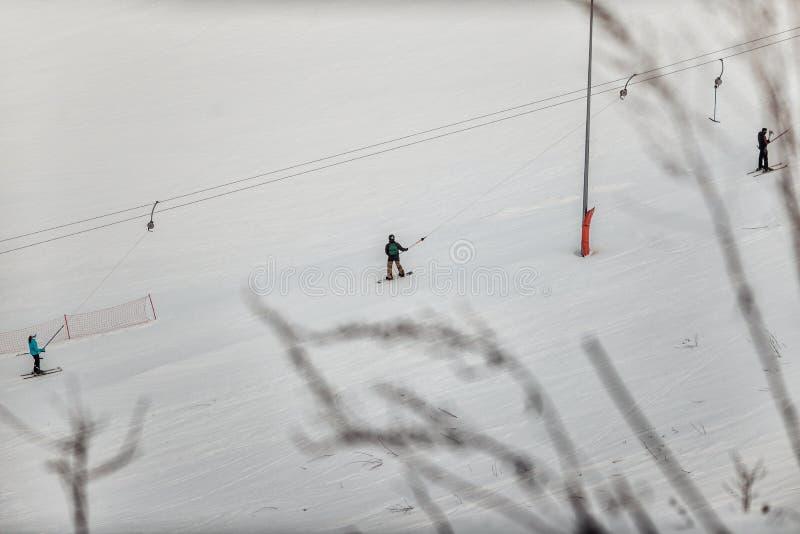黑盔甲骑马的挡雪板在一条多雪的轨道 库存照片