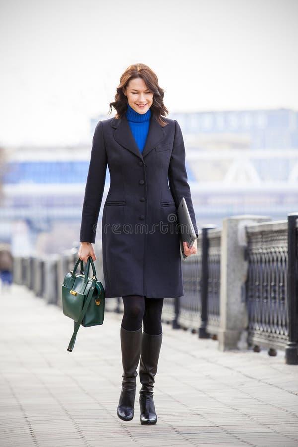 黑眼睛表面方式性感的样式妇女 女实业家 一黑色大衣的一名美丽的微笑的中年妇女有一台膝上型计算机和一个绿色提包的在她 免版税库存图片