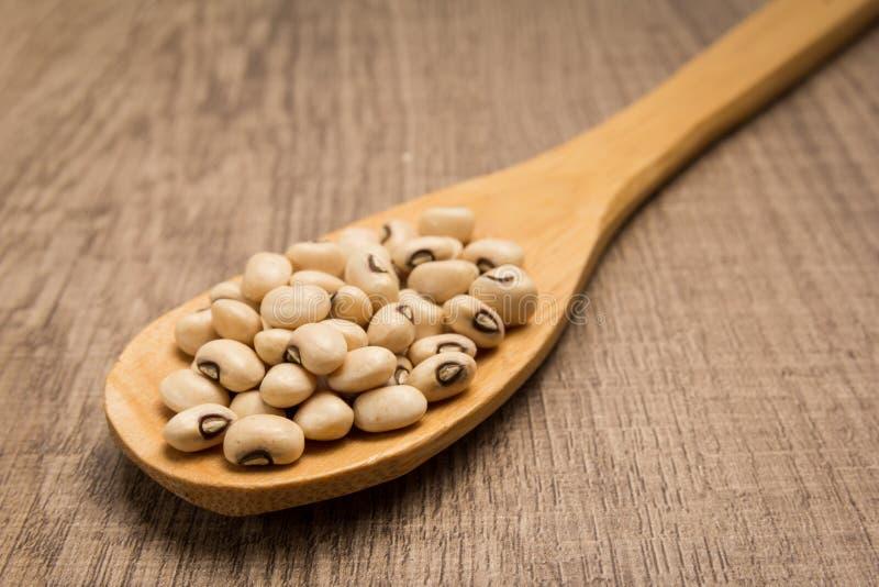 黑眼豆豆类 匙子和五谷在木桌 库存图片