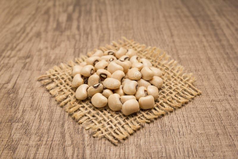 黑眼豆豆类 在黄麻方形的保险开关的五谷  木t 免版税库存图片