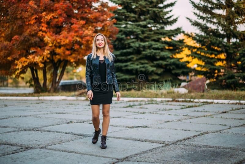黑短的礼服和皮夹克的性感的妇女通过公园走户外 库存图片