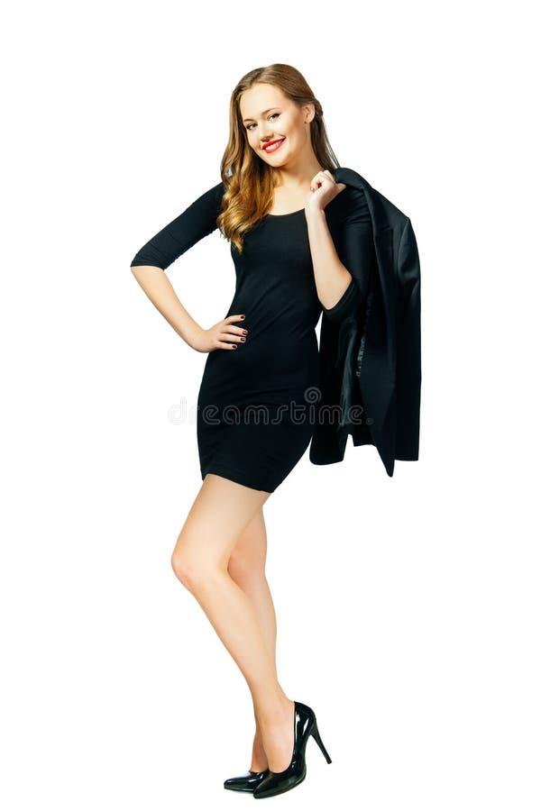 黑短的礼服的年轻美女举行在她的肩膀的夹克和神色在照相机 查出 免版税图库摄影