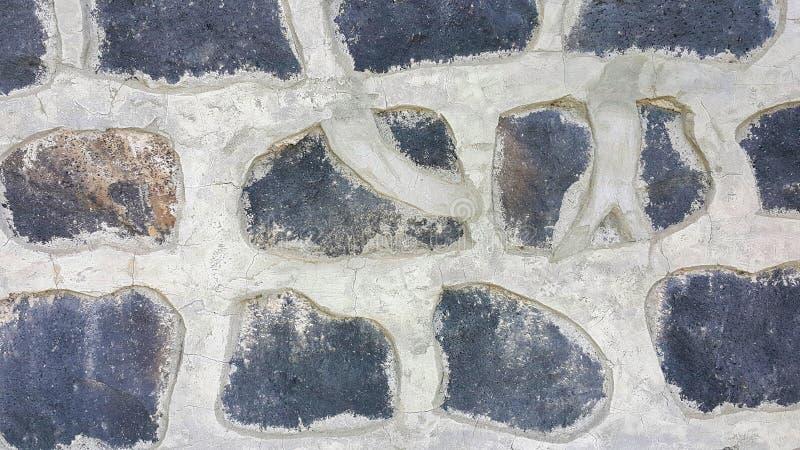 黑石墙,纹理篱芭,石头放置和固定与具体,可看见的被仿造的具体重灰色线 免版税图库摄影