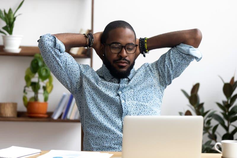 黑确信的工作者结束打工坐的休息在办公室des 免版税库存照片