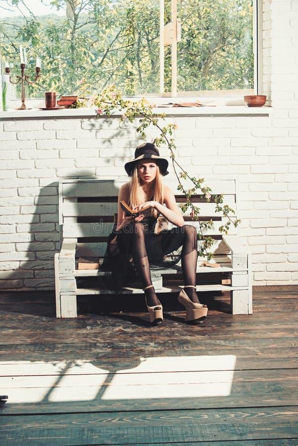 黑礼服和减速火箭的帽子的俏丽的女孩 在浪漫作家的诗书 时尚妇女模型读了书 春天或 免版税库存图片