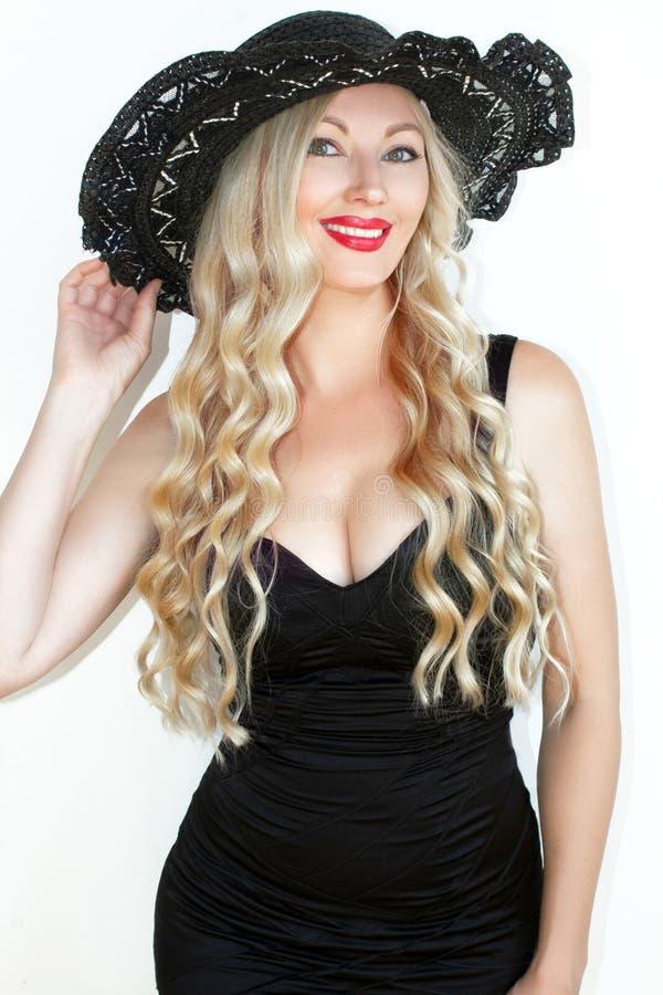 黑礼服和帽子的美丽的少妇金发碧眼的女人有低颈露肩的 库存图片