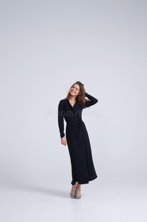 黑礼服摆在的惊人的女孩 免版税库存照片