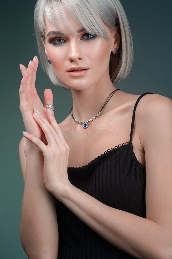 黑礼服现代样式的秀丽和首饰妇女与发型和银色bijouterie 与项链的时尚白肤金发的模型 免版税库存照片