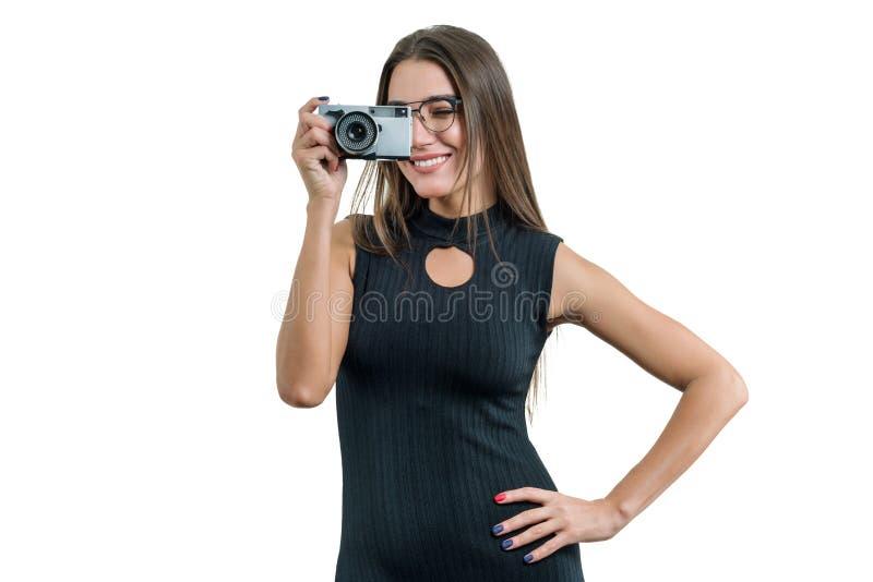 黑礼服玻璃的年轻微笑的美女在她的手上的拿着照片照相机,照相,在白色被隔绝的背景 库存图片