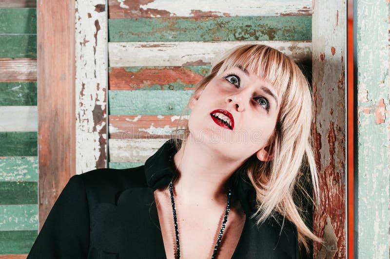 黑礼服的一个相当白肤金发的女孩嬉戏地微笑 免版税图库摄影